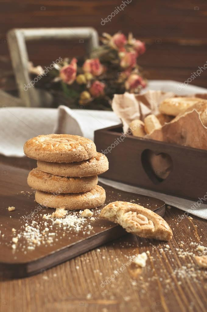 Lot of cookies and dry roses on wooden plank