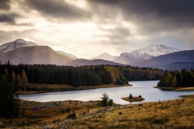 Autumn landscape in Highlands, Scotland, United Kingdom. Beautiful mountains with snow in background. stock vector