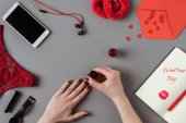 cropped image of woman painting nails with red polish, notebook with words valentines day