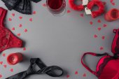 Fotografie top view of panties, bra and handcuffs with glass of wine on table