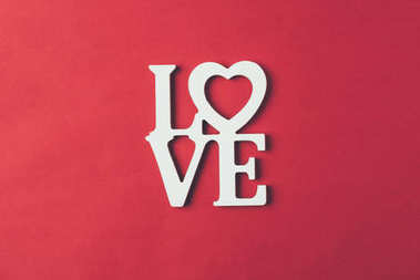top view of white sign with word love isolated on red