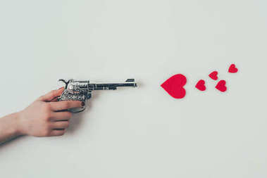 cropped image of woman aiming gun at paper hearts on white, valentines day concept