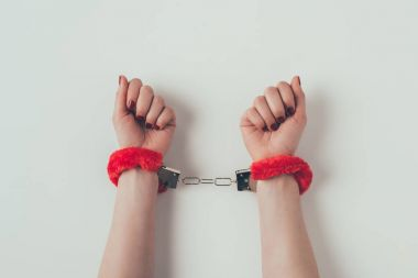 cropped image of woman hands in red fluffy handcuffs on white, valentines day concept