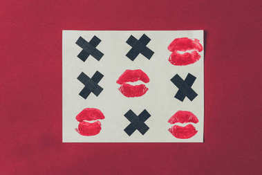 Top view of tic-tac-toe with black crosses and lips prints isolated on red, valentines day concept stock vector