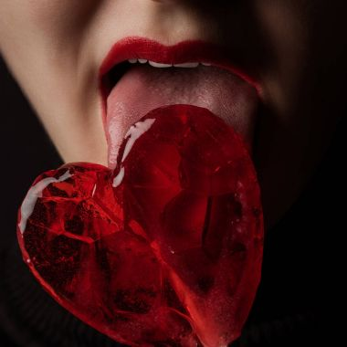 cropped image of woman licking heart shaped lollipop isolated on black, valentines day concept