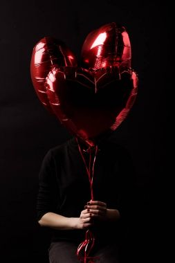 woman holding bundle of heart shaped balloons in hands isolated on black, valentines day concept