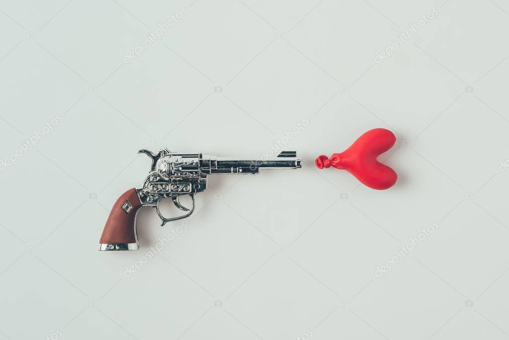 top view of gun aiming at heart shaped balloon isolated on white, valentines day concept