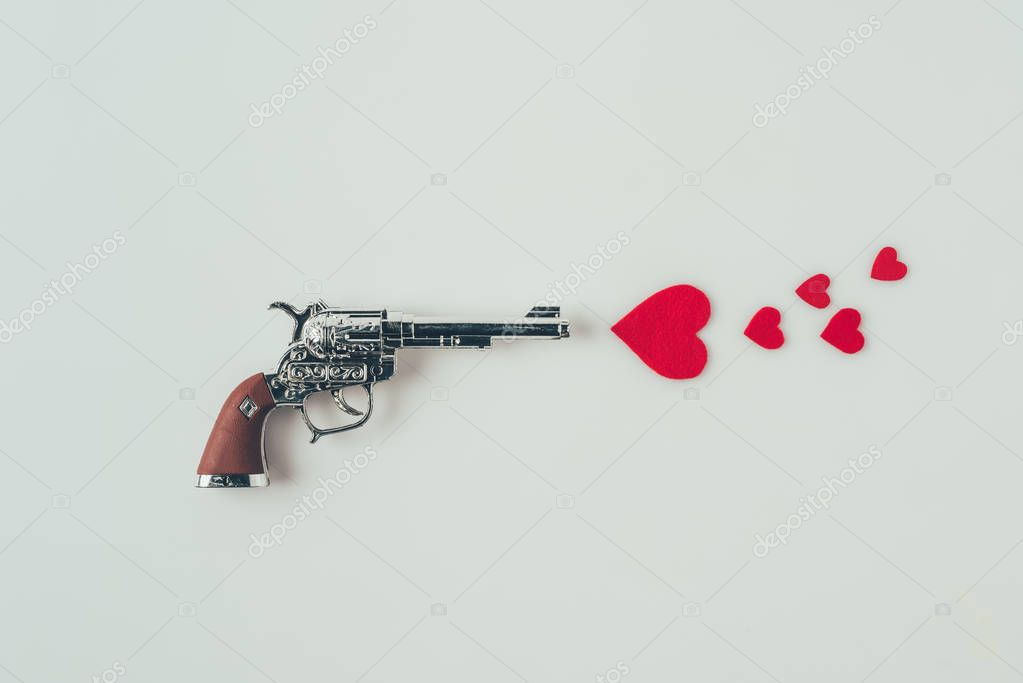 top view of gun aiming at paper hearts isolated on white, valentines day concept