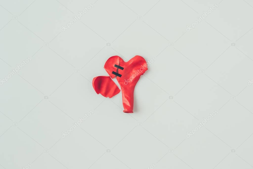 top view of broken heart shaped balloon with insulating tape isolated on white, valentines day concept