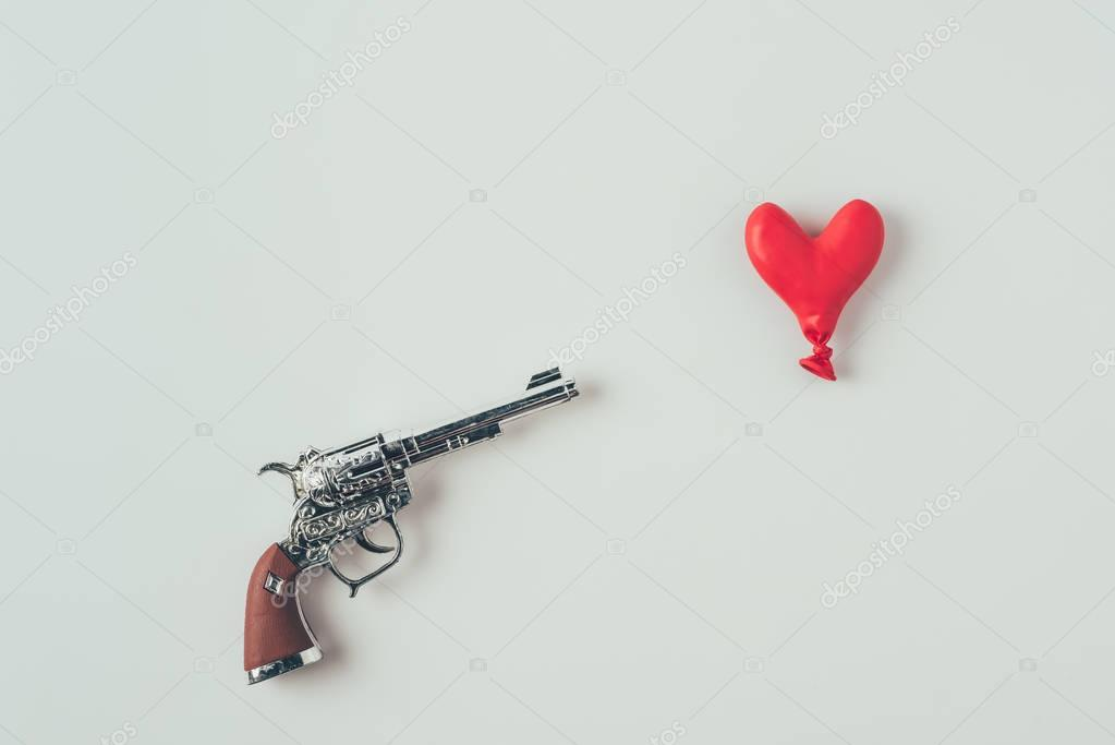top view of gun barrel aiming at heart shaped balloon isolated on white, valentines day concept