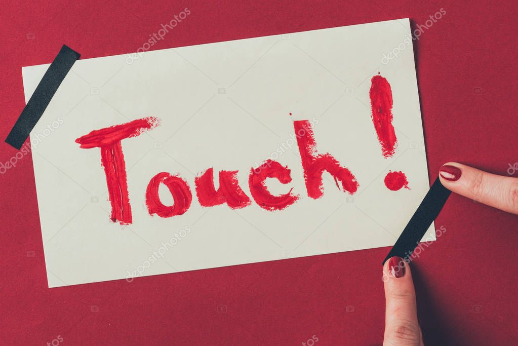 cropped image of woman putting insulating tape on note with word touch, valentines day concept