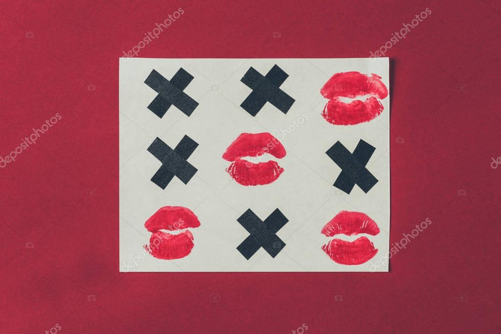 top view of tic-tac-toe with black crosses and lips prints isolated on red, valentines day concept