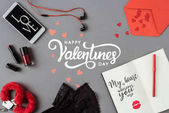 Fotografie Top view of words happy valentines day between smartphone and notebook on gray surface