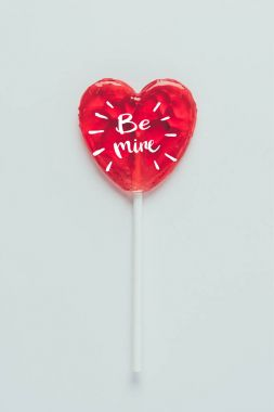 Top view of heart shaped lollipop with words be mine isolated on white