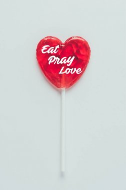 Top view of heart shaped lollipop with words eat pray love isolated on white