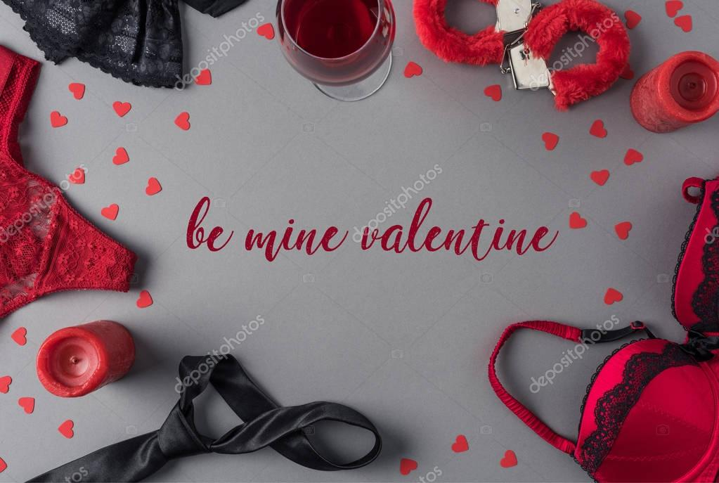 Top view of words be mine valentine between underwear and glass of wine