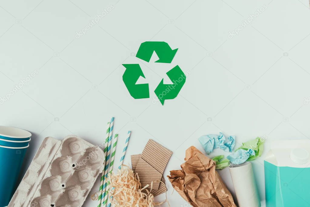 flat lay with various types of garbage and recycle sign isolated on grey