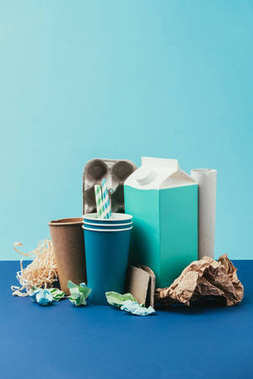 close up view of arranged cardboard and paper disposable garbage on blue background