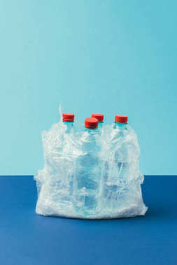 close up view of plastic bottles in plastic bag on blue background, recycle concept