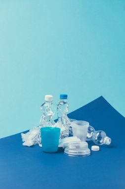 close up view of various plastic trash on blue background, recycle concept