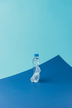 close up view of plastic bottle on blue background, recycle concept
