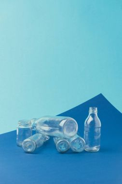 close up view of various glass bottles and jars on blue background, recycle concept