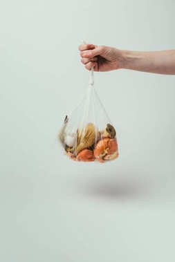 cropped shot of woman holding plastic bag with trash on grey background