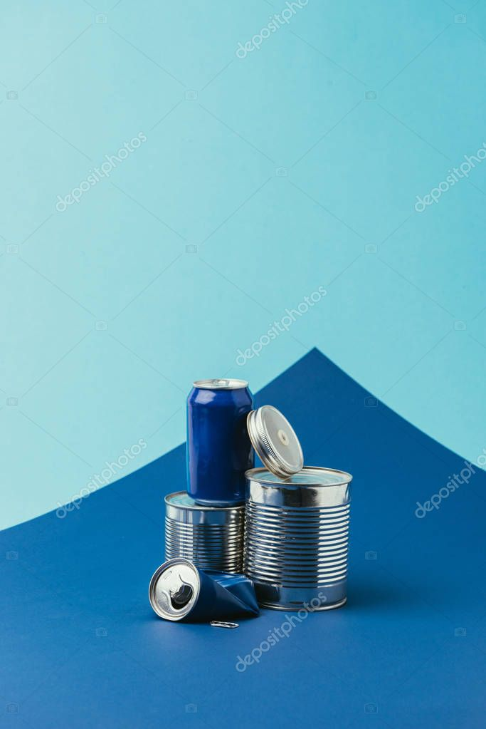 close up view of arranged metal cans on blue background, recycle concept