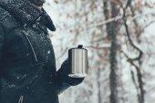 részleges kilátás nyílik nő holding thermocup forró itallal a téli nap