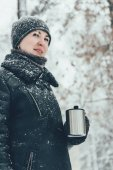 portrét usmívající se žena s termohrnek s horkým nápojem, koukal na ulici, kterou jsem v zimě