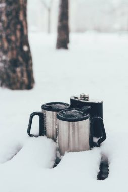 close up view of thermocups and flask in snow on winter day in forest