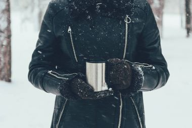 partial view of woman holding thermocup with hot drink on winter day