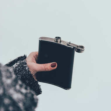 cropped shot of woman holding flask in hand on winter day