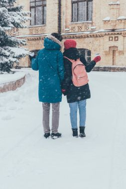 back view of couple with thermocups holding hands in winter