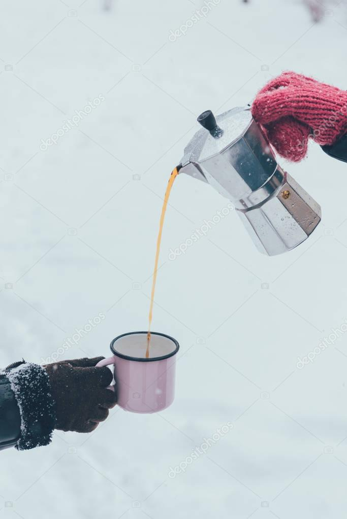partial view of man pouring hot coffee into cup on winter day
