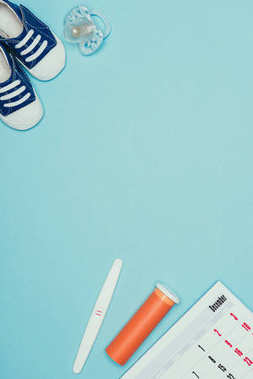 top view of childish shoes, pacifier, calendar, pregnancy test and contraceptive isolated on blue