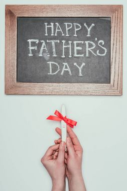 cropped shot of woman holding pregnancy test with ribbon and happy fathers day lettering on blackboard isolated on grey