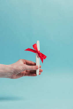 cropped shot of woman holding pregnancy test with ribbon isolated on blue