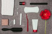 Fotografie Draufsicht der Anordnung der verschiedenen Damenhygiene Verbrauchsmaterialien und Blume auf graue Oberfläche