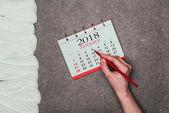 oříznutý snímek ženy ukazující na datum v kalendáři s menstruační tampony kolem na šedém povrchu