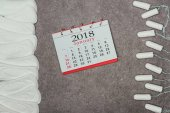 Fotografie Ansicht von oben angeordneten Menstruationsauflagen, Tampons und Kalender auf graue Oberfläche