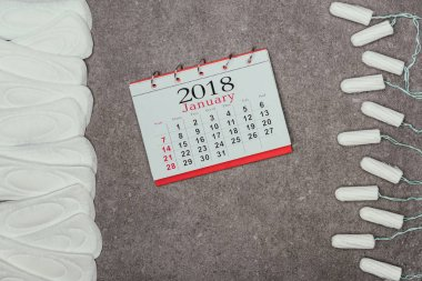 top view of arranged menstrual pads, tampons and calendar on grey surface