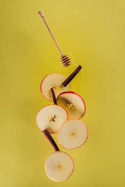 close up view of levitating pieces of apple, cinnamon sticks and honey