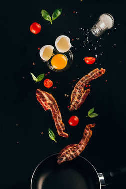 Close up view of pieces of bacon, cherry tomatoes and raw egg yolk falling on frying pan isolated on black stock vector