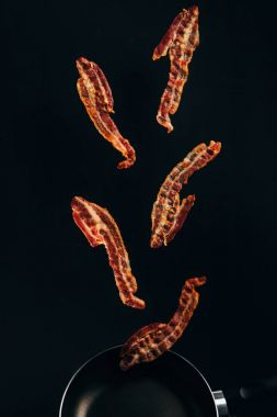 Close up view of pieces of bacon falling on frying pan isolated on black stock vector