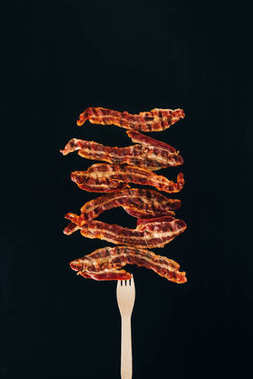 Close up view of pieces of bacon on fork isolated on black stock vector
