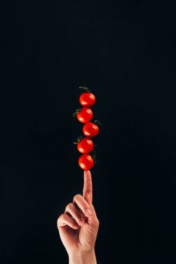 cropped shot of woman holding cherry tomatoes on finger isolated on black