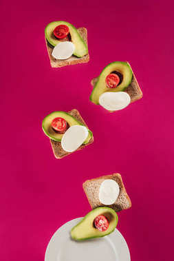 close up view of toasts, avocado pieces, mozzarella cheese and cherry tomatoes falling on plate isolated on pink