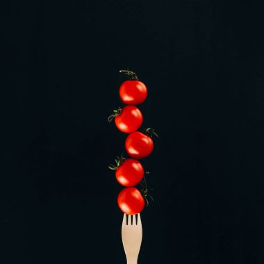 close up view of levitating cherry tomatoes on fork isolated on black