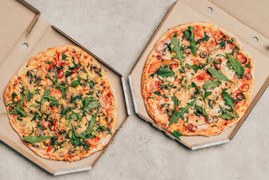 Hot Italian pizzas with arugula in cardboard boxes on light background